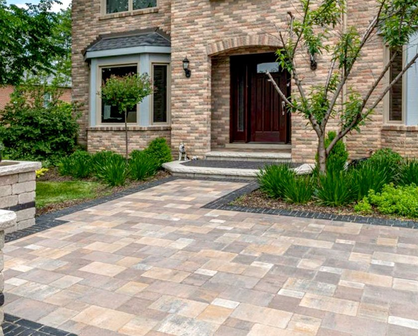 Paver patio leading up to home with front landscape