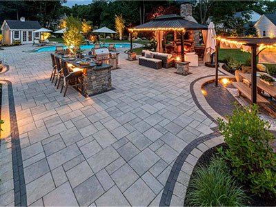 Large outdoor living space with large patio, island, pergola with sitting areas, and pool in the background