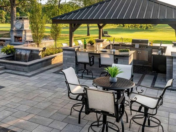 Patio with covered outdoor kitchen and dining area and fire place and water feature
